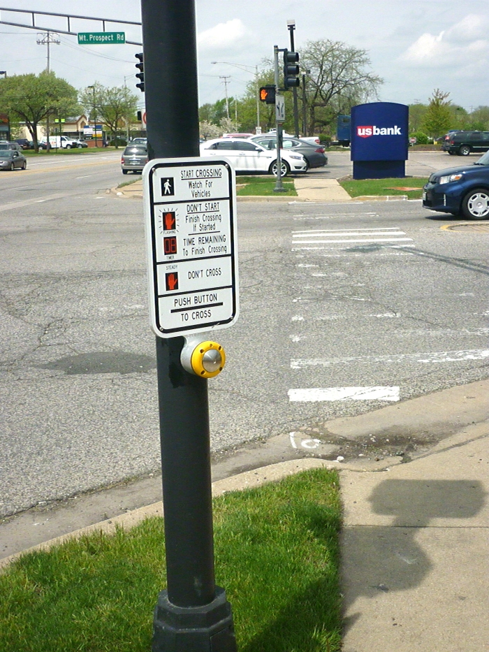 Pedestrian amenities, such as this crosswalk signal at Rand Road and Mount Prospect Road, are helpful but inconsistently incorporated throughout the full corridor.
